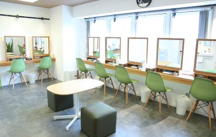 明るい日差しが差し込みL字型にセルフエステ用の木目調のテーブル、テーブル前には大きな鏡とグリーンの椅子が7席、中央にカウンセリング用の木目調のセンターテーブルとグリーンの椅子が配置されたメインルームの写真