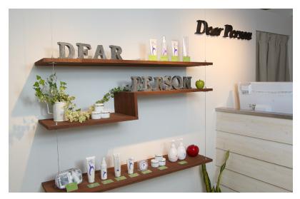 間接照明に映し出された活性水素化粧、観葉植物、DEARPERSONと型どられたブリキの小物が並ぶカウンター横のディスプレイ棚の写真