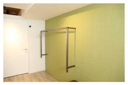 淡いグリーンの壁に備え付けられたお客様の上着をかけるステンレスのクロークとハンガー。奥には個室の施術部屋のまっ白なドアが見える写真