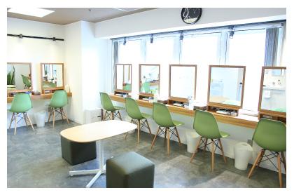 明るい日差しが差し込む白とグリーンに統一されたセルフエステを行う部屋。壁に沿ってL字に木目のテーブルと大きな鏡、グリーンの椅子が備え付けられ、部屋の中央にはカウンセリング用のテーブルと椅子が置いてある写真