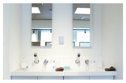 清潔感ある白のシンクに目の前の壁には大きな鏡がかけられた洗面台の写真