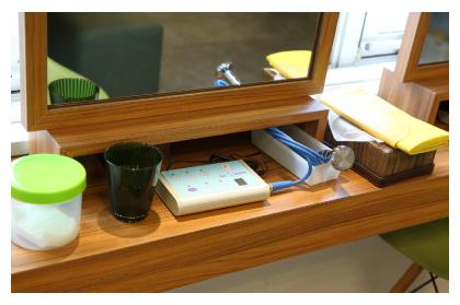 大きな鏡と木目のテーブルにセルフエステ用にセットされた超音波美顔器とコップに入った活性水素水、黄色のケープが置いてある写真