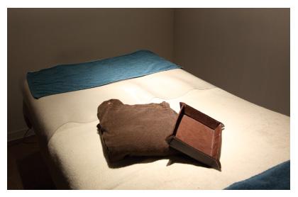 施術部屋ベッドの上にたたまれた着替え用のガウンがスポットライトに照らし出されている写真