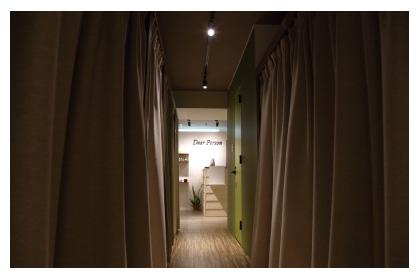 両サイドをベージュのカーテンで仕切られ、施術部屋から受付方向をスポットライトで照らされた通路の写真