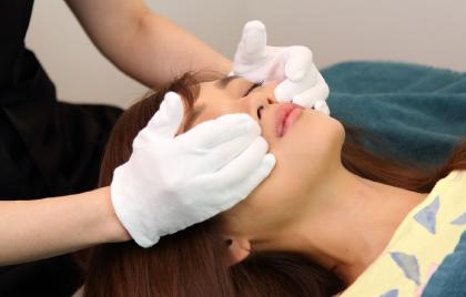 白い手袋をしたスタッフが寝ている女性の頬骨の下のコリをほぐしている造顔マッサージの様子