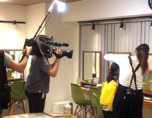 セルフエステ鏡前でどさんこワイド179のレポーターさんにスタッフが超音波美顔器をあてているところを照明をあてながらテレビカメラマンが撮影している様子