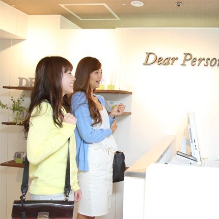はじめてご来店の女性2人が明るい受付前で笑顔でスタッフに語りかけている様子