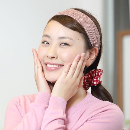 女性が笑顔でエステで潤った頬に手をあてている写真
