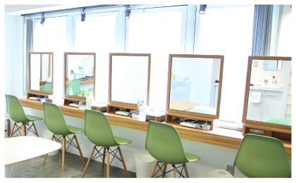 窓から明るい日差しが差し込み、鏡と椅子4台が並んでるセルフエステ施術部屋のようす風景