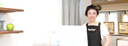 受付カウンターで笑顔でお客様を迎えるオーナーの写真
