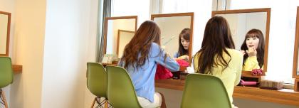 施術を終えた女性2人が鏡の前でゆっくり帰りのお化粧をしている様子