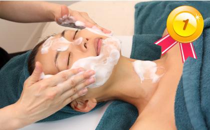 仰向けでベッドに寝ている女性の頬にスタッフが手を添えふわふわの泡でホワイトニング洗顔している肌改善ベーシックコースの様子