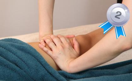 仰向けでベッドに寝ている女性の脚の膝上をスタッフがリンパマッサージしている全身リンパドレナージュの様子