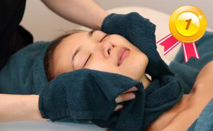 仰向けでベッドに寝ている女性の頬にスタッフがホットタオルでケアしている至福のプレミアムボディ&フェイシャルの様子