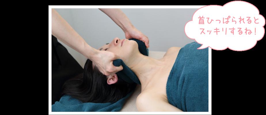 愛さんの首の下に温かい蒸しタオルを入れ、頸椎を伸ばすようにひっぱっている写真。「首ひっぱられるとスッキリするね!」と愛さんのコメント