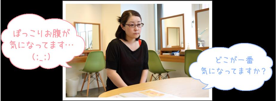 奥にはセルフエステのテーブルと椅子が並ぶメインルーム中央のテーブル越しに座り「どこが一番気になってますか?」のオーナーの問いに「ぽっこりお腹が気になってます…(:_;)」とちょっと恥ずかしそうに答える奈緒子さんの写真