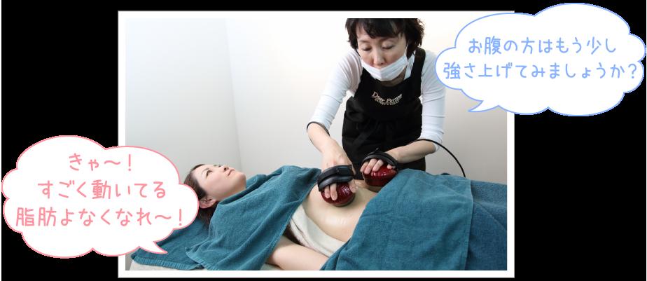 仰向けに寝ている奈緒子さんのお腹に「お腹の方はもう少し強さを上げてみましょうか?」と聞きながらツインヘッドをあてていくオーナー。「きゃ~!すごく動いてる。脂肪よなくなれ~!」と楽しげな表情の奈緒子さんの写真