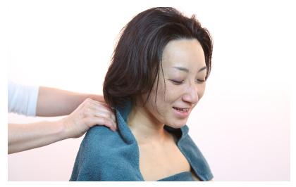 施術後に肩にタオルをかけジェルを拭いてもらっているすっきりして笑顔の女性の写真