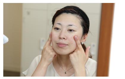 鏡を覗き込みながら頬の弾力を指で確認している女性の写真