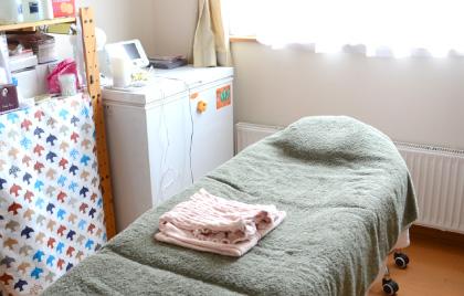 室内中央の整えられたベッドの上にお着替え用のガウンが置かれ、横にはお化粧品が並べられた木製のラックとアロマオイルが置かれた施術部屋のようす写真