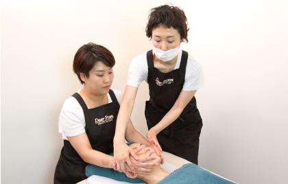 研修者がベッドに寝ている練習モデルの顔に手をあて、横に立つオーナーが研修者の手をとり指導している様子