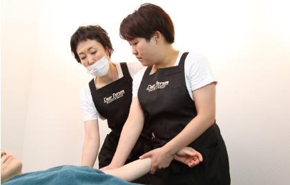 研修者がベッドに寝ている練習モデルの腕を手にとりマッサージし、横に立つオーナーが手を添えて指導している様子