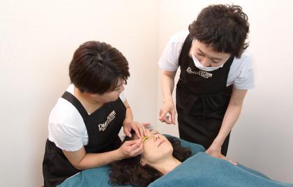 椅子に座った研修者がベッドに寝ている練習モデルのまつげを巻き、横に立つオーナーがチェックし指導している様子