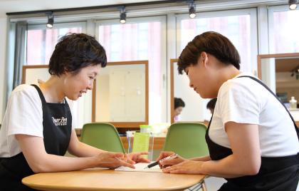 カウンセリング用のテーブルに研修者とオーナーが向かい合って座り、カウンセリングシートを見ながらオーナーが指導している様子