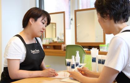化粧品を並べたテーブルに研修者とオーナーが向かい合って座り、オーナーが化粧品を手にとり必要な知識を研修者に説明している様子