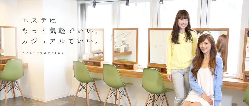 エステはもっと気軽でいい。カジュアルでいい。beauty&relax 明るい日差しが差し込む白を基調としたセルフエステルームにはL字に木目のテーブルが設置され、8席分のグリーンの椅子と大きな鏡が一席ごとにスポットライトで照らし出され、右手前で椅子に座った女性とその横で椅子に手をかけ立っている女性が笑顔で頬笑みかけている写真